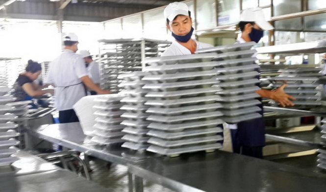 Nhân viên nhà n ang chu©n bË su¥t n giïa tr°a cho công nhân t¡i mÙt công ty trên Ëa bàn Óng Nai - ¢nh: A LÙc